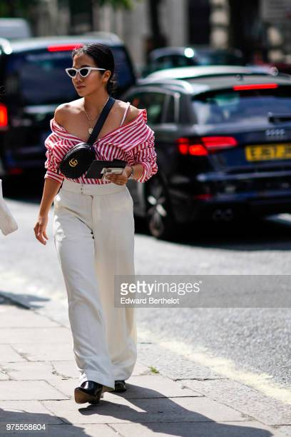 A guest wears sunglasses a Gucci black shoulder strapped bag offshoulder striped red and white top white pants sunglasses during London Fashion Week...