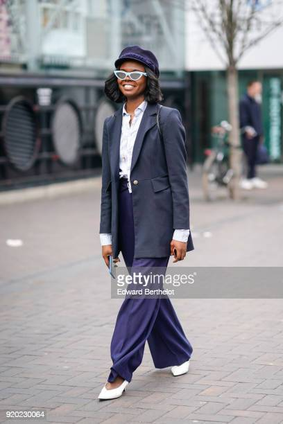 Guest wears sunglasses, a hat, a blazer jacket, purple pants, white shoes, a white shirt, during London Fashion Week February 2018 on February 18,...