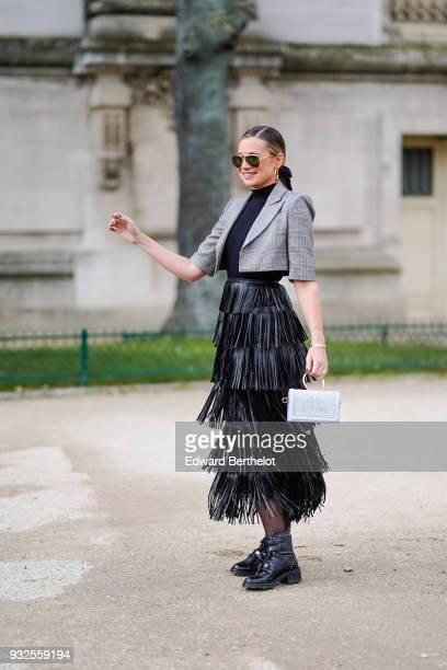 A guest wears sunglasses a highneck top large creole earrings a grey princeofwales checkered bolero jacket a black fringe long skirt a grey handbag...