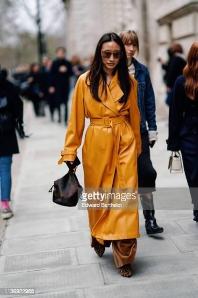 A guest wears sunglasses a honey color oversize maxi coat a brown handbag brown velvet wideleg pants leopard print pointy pumps during London Fashion...