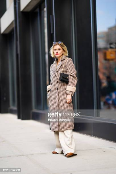 Guest wears sunglasses, a houndstooth pattern printed wool long double breasted coat, a bag from Gucci, white flared pants, brown leather pointy...