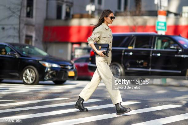 A guest wears sunglasses a jumpsuit a black leather bag black leather shoes outside Tory Burch during New York Fashion Week Fall Winter 2020 on...