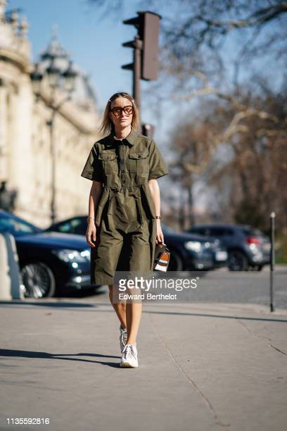 A guest wears sunglasses a khaki dress a white bag with tan blue and brown stripes white and grey sneakers outside Unravel Project during Paris...