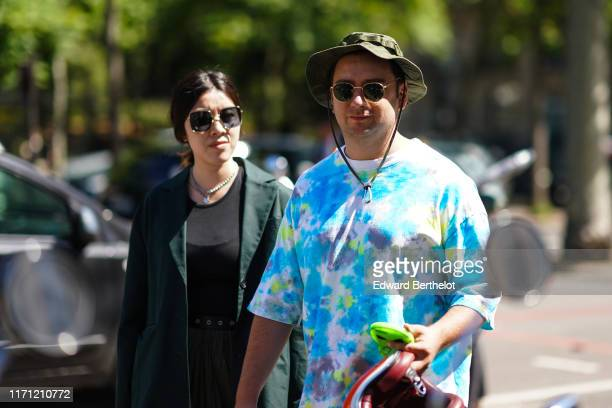 Guest wears sunglasses, a khaki military hat, a watercolor white, blue and yellow t-shirt , during Paris Fashion Week - Menswear Spring/Summer 2020,...
