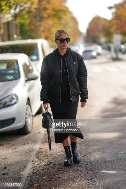 A guest wears sunglasses a Lacoste bomber jacket a black skirt a bag black leather shoes outside Lacoste during Paris Fashion Week Womenswear Spring...