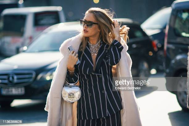 Guest wears sunglasses, a large glittering necklace, a white fluffy coat, a white thin striped black jacket, a studded clear vinyl round handbag,...