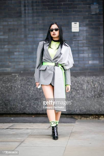 A guest wears sunglasses a large light grey scarf a neon green top a grey jacket a light green belt shiny black pointy ankle boots during London...