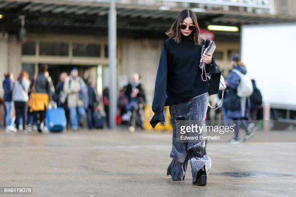 A guest wears sunglasses a large oversized black pull over with long sleeves large pants and shoes with large heels outside the Olivier Theyskens...
