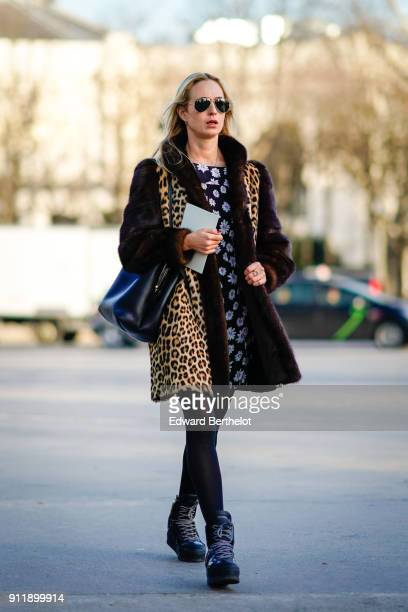A guest wears sunglasses a leopard print coat with fur a flower print black and white dress outside Chanel during Paris Fashion Week Haute Couture...