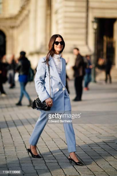 A guest wears sunglasses a light blue pantsuit a black Chanel bag with a pompon black slingback pumps outside Louis Vuitton during Paris Fashion Week...