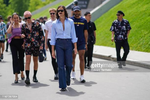 A guest wears sunglasses a light blue shirt navy blue denim cuffed pants black shoes outside Kenzo during Paris Fashion Week Menswear Spring/Summer...