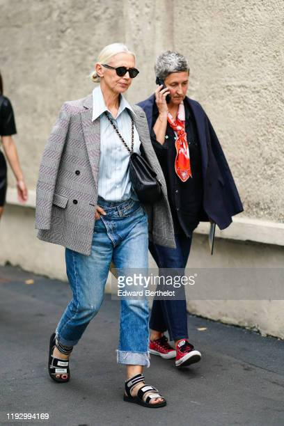 Guest wears sunglasses, a light blue shirt with thin black stripes, a grey Prince of Wales double-breasted jacket, a black bag, blue denim pants with...