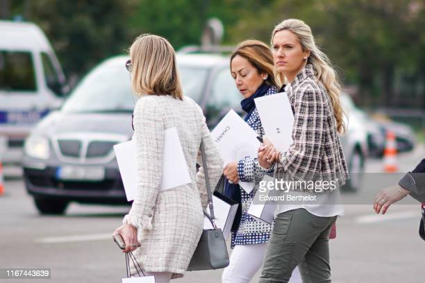 A guest wears sunglasses a light grey fringed tweed coat a grey bag A guest wears a navy blue turtleneck a navy blue and grey jacket white pants A...