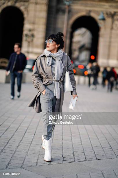 A guest wears sunglasses a light grey scarf a grey camouflage top a half grey half beige trench coat grey pants a white tote bag white boots outside...