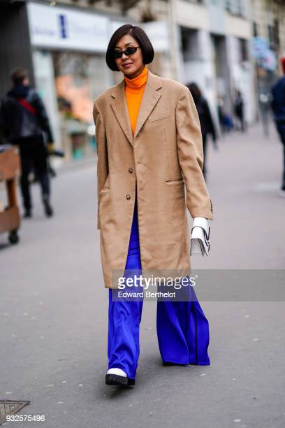 A guest wears sunglasses a long brown blazer jacket coat blue large flare pants during Paris Fashion Week Womenswear Fall/Winter 2018/2019 on March 3...