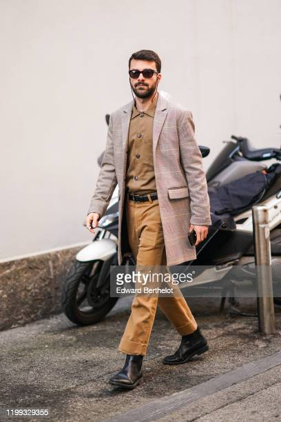 A guest wears sunglasses a long jacket with printed checked patterns a brown shirt a belt brown pants black leather boots outside Spyder during Milan...