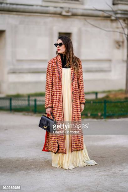 A guest wears sunglasses a long orange houndstooth tweed coat a black turtleneck a flowy beige pleated maxi dress a black handbag during Paris...