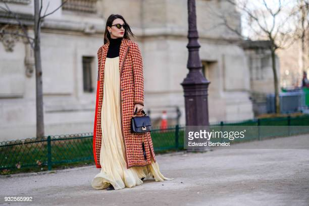 A guest wears sunglasses a long orange houndstooth tweed coat a black turtleneck a beige flowy pleated maxi dress a black handbag during Paris...
