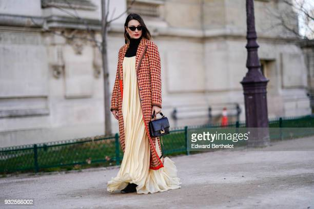 A guest wears sunglasses a long orange houndstooth tweed coat a black turtleneck a flowy beige pleated maxi dress a black handbag black shoes during...