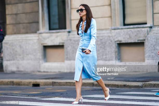 Guest wears sunglasses, a low neck blue lustrous silky dress, white high heeled shoes, outside the Bottega Veneta show during Milan Fashion Week...