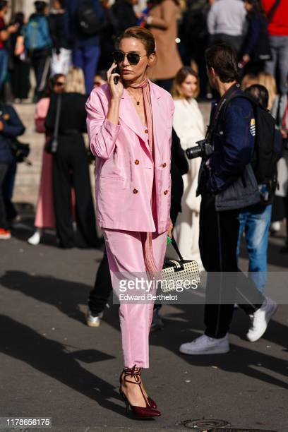 A guest wears sunglasses a lustrous pale pink doublebreasted pantsuit a fringed pink and beige scarf brown Tstrap pointy heels a cannage embellished...