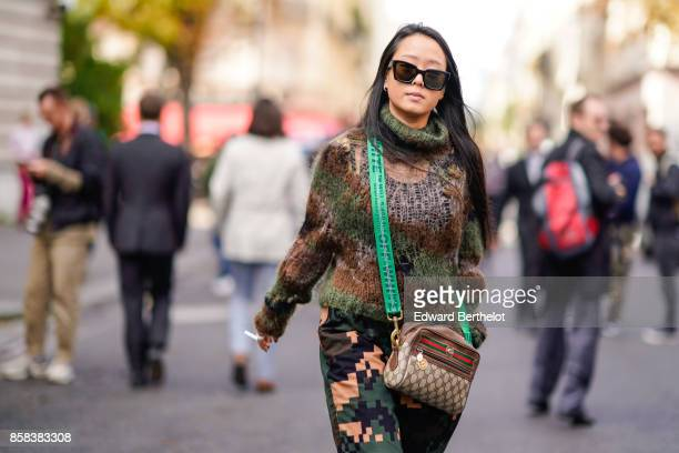 A guest wears sunglasses a military camo print turtleneck wool pull over a Gucci bag outside Moncler during Paris Fashion Week Womenswear...