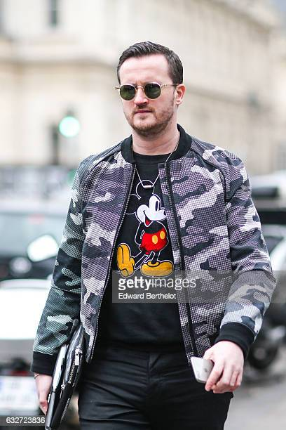 A guest wears sunglasses a military camouflage gray bomber jacket a black tshirt with a printed Mickey Mouse outside the Jean Paul Gaultier show...