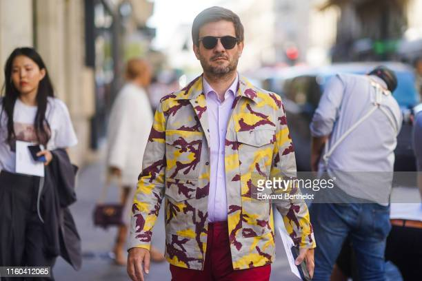 A guest wears sunglasses a military camouflage print jacket pale purple shirt red pants outside Valentino during Paris Fashion Week Haute Couture...