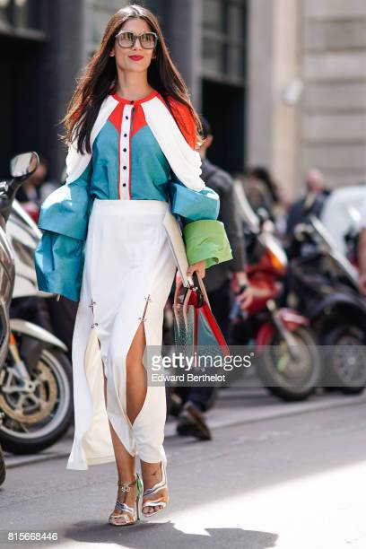 A guest wears sunglasses a multi color top a white skirt silver heels shoes outside the Elie Saab show during Paris Fashion Week Haute Couture...