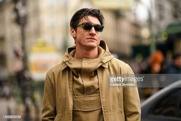 Guest wears sunglasses, a Napapijri sand-color hooded top, a Napapijri matched jacket, outside Paul Smith, during Paris Fashion Week - Menswear...