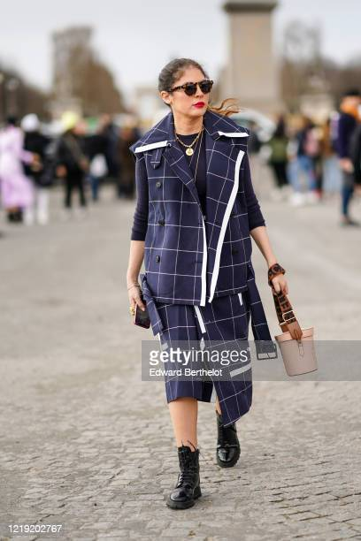 Guest wears sunglasses, a navy blue checked jacket, a black top, a golden necklace, a skirt, black leather shoes, a bag, outside Dior, during Paris...