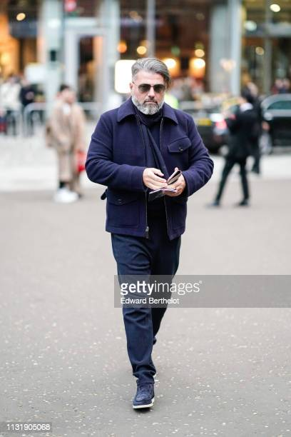A guest wears sunglasses a navy blue jacket navy blue pants navy blue suede moccasins outside Burberry during London Fashion Week February 2019 on...