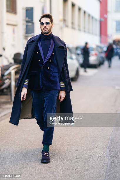Guest wears sunglasses, a navy blue long coat, a turtleneck pullover, a blue velvet double breasted jacket with purple parts, blue pants, green...