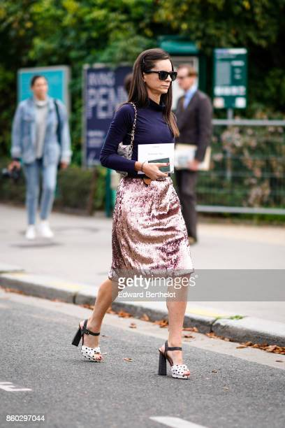 A guest wears sunglasses a navy blue turtleneck top a grey and pink bag a pink lame skirt black and white spotted platform shoes outside Lanvin...