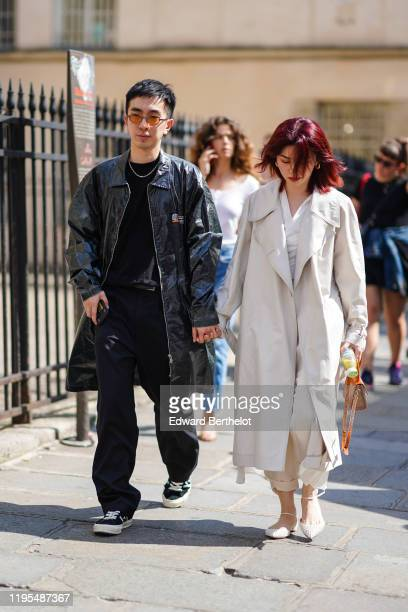 Guest wears sunglasses, a necklace, a black top, a shiny black trench coat, black full-length pants with thin white stripes, black sneakers ; A guest...