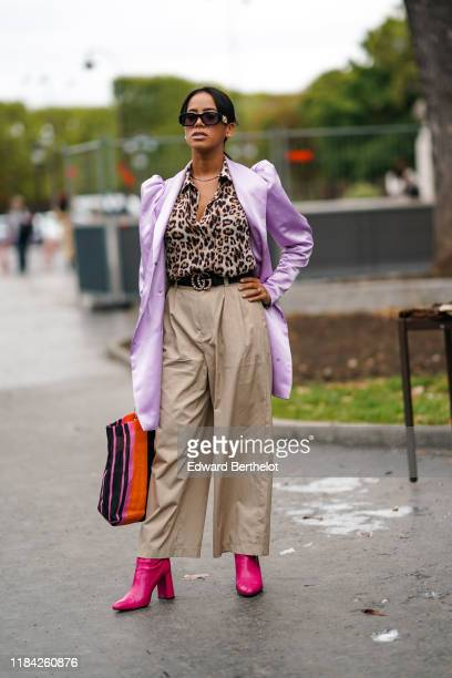 Guest wears sunglasses, a necklace, a leopard print shirt, a light purple long jacket with leg-of-mutton sleeves, a black Gucci belt, sand-color...