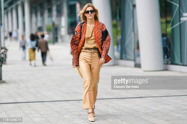 A guest wears sunglasses a necklace a sandcolor top a paisley design quilted orange jacket a bejeweled belt sandcolor leather laceup flare pants...