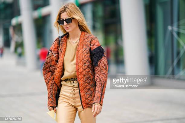 A guest wears sunglasses a necklace a sandcolor top a paisley design quilted orange jacket a bejeweled belt sandcolor leather laceup pants outside...