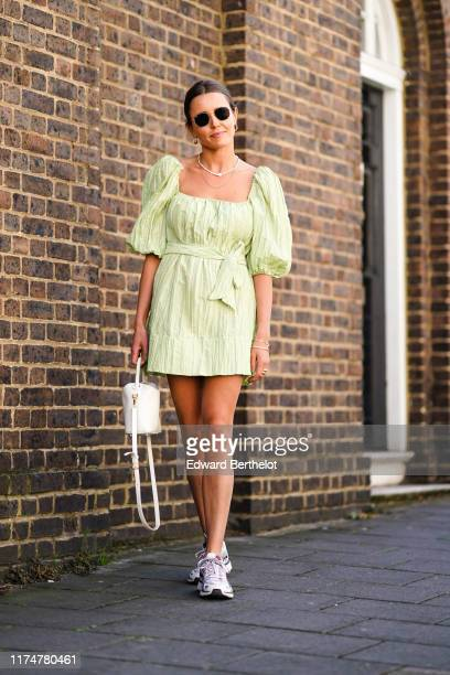 A guest wears sunglasses a necklace a white bag a pale green dress with puff shoulders sneakers shoes during London Fashion Week September 2019 on...