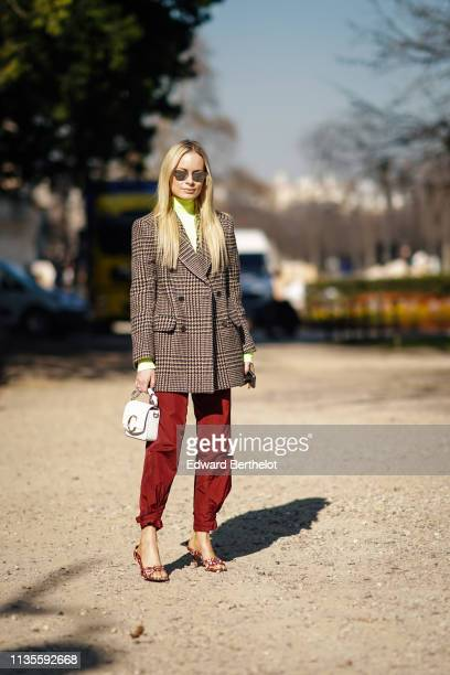 A guest wears sunglasses a neon green turtleneck a brown Prince of Wales check double breasted jacket a white Chloe bag rust color pants red and...