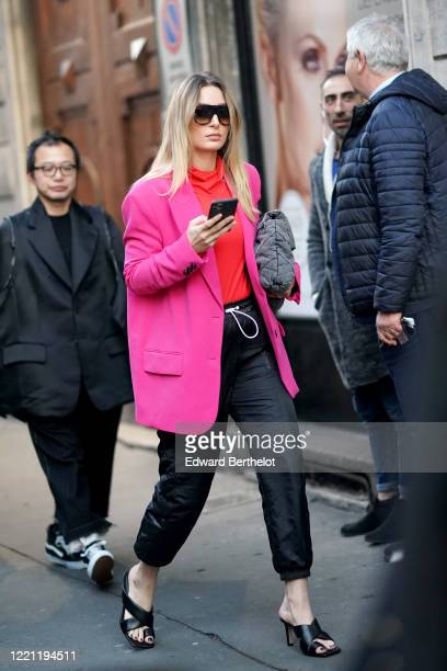 Guest wears sunglasses, a neon pink oversized blazer jacket, a red top, black cropped pants, leather shoes, outside N°21, during Milan Fashion Week...