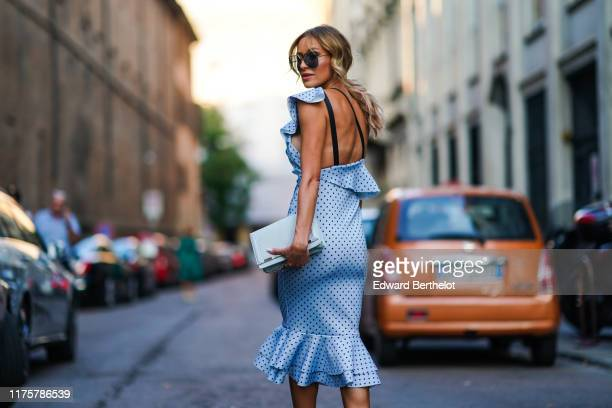 A guest wears sunglasses a oneshoulder ruffled blue dress with printed polka dots a light blue turquoise bag outside the Bottega Veneta show during...