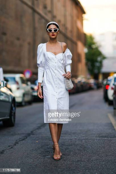 Guest wears sunglasses, a one-shoulder ruffled white dress with buttons, a beaded bag, a headband, outside the Bottega Veneta show during Milan...