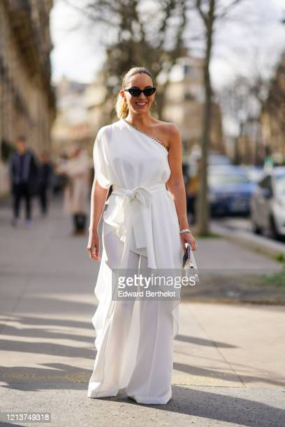 Guest wears sunglasses, a one-shoulder white dress, flared flowing pants, earrings, outside Elie Saab, during Paris Fashion Week - Womenswear...