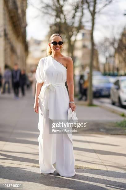 Guest wears sunglasses, a one-shoulder white dress, flared flowing pants, earrings, outside Elie Saab, during Paris Fashion Week - Womenswear...