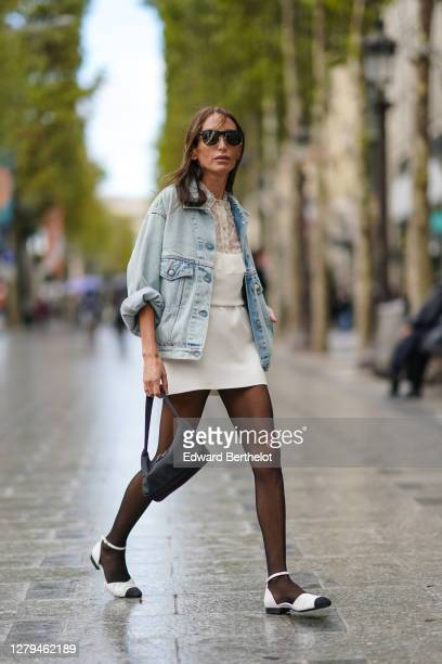 Guest wears sunglasses, a pale blue denim jacket, a white dress, a black Prada bag, black tights, white flat shoes with black tip, outside Miu Miu,...