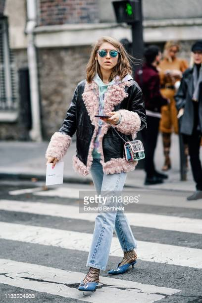 Guest wears sunglasses, a pale blue hooded sweatshirt, a shiny black jacket lined with pink fur, a see through Chanel bag, black fishnet socks, shiny...