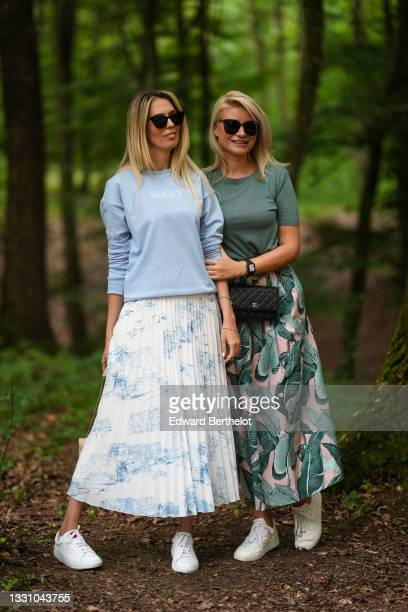 Guest wears sunglasses, a pale blue Hugo Boss pullover, a white with blue print pattern pleated / accordion midi skirt, white leather sneakers,...