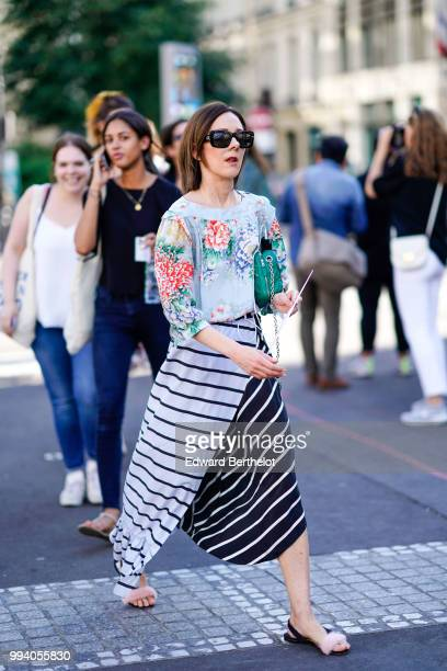 A guest wears sunglasses a pale blue top with printed red and blue flowers a black and white striped skirt outside Fendi during Paris Fashion Week...