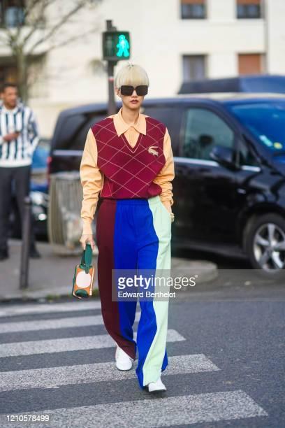 Guest wears sunglasses, a pale orange polo shirt, a sleeveless v-neck Lacoste argyle print burgundy pullover, blue green purple striped pants, a bag...
